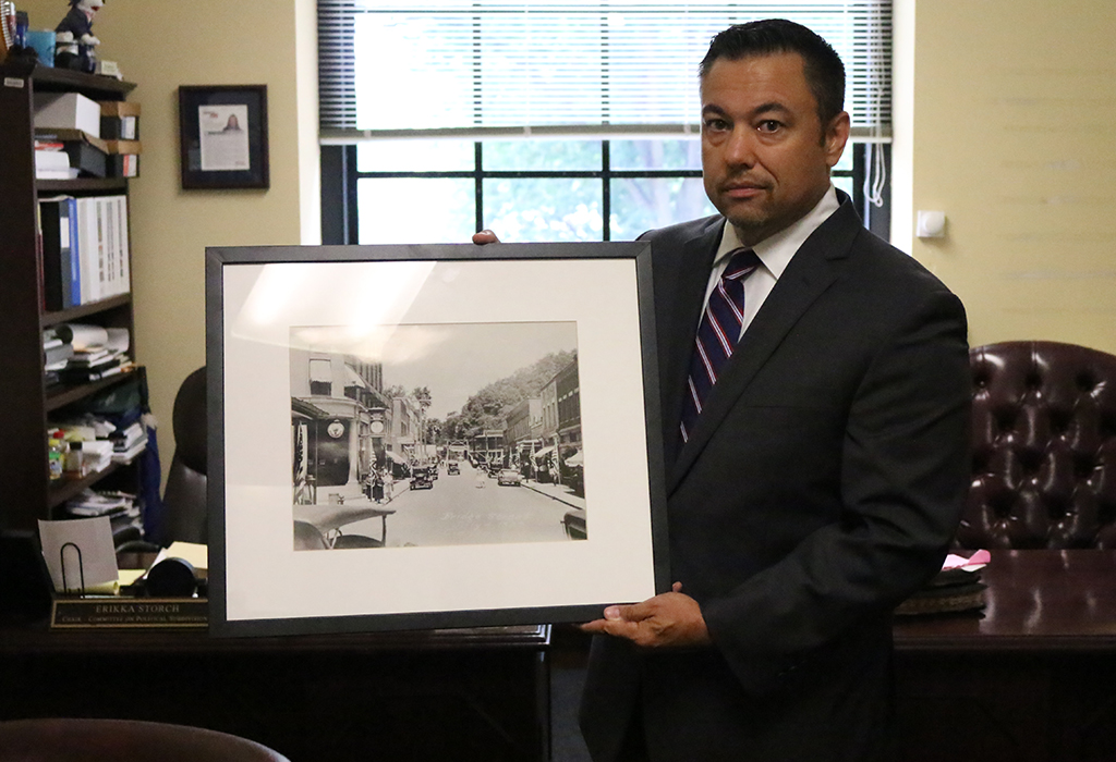 Dean Jeffries with picture of downtown Clendenin in 1929 for his new office. Photo Credit - Mark Burdette